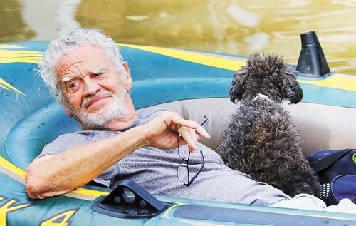 一男人帶著他的狗撤離到安全地帶。法新社