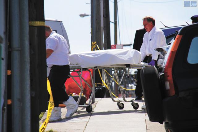 檢驗人員將屍體抬出屋外。本報資料圖片