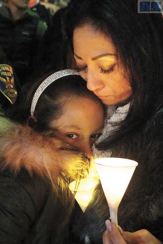 女孩在母親懷抱中,燭光在寒風中搖曳。記者黃偉江攝