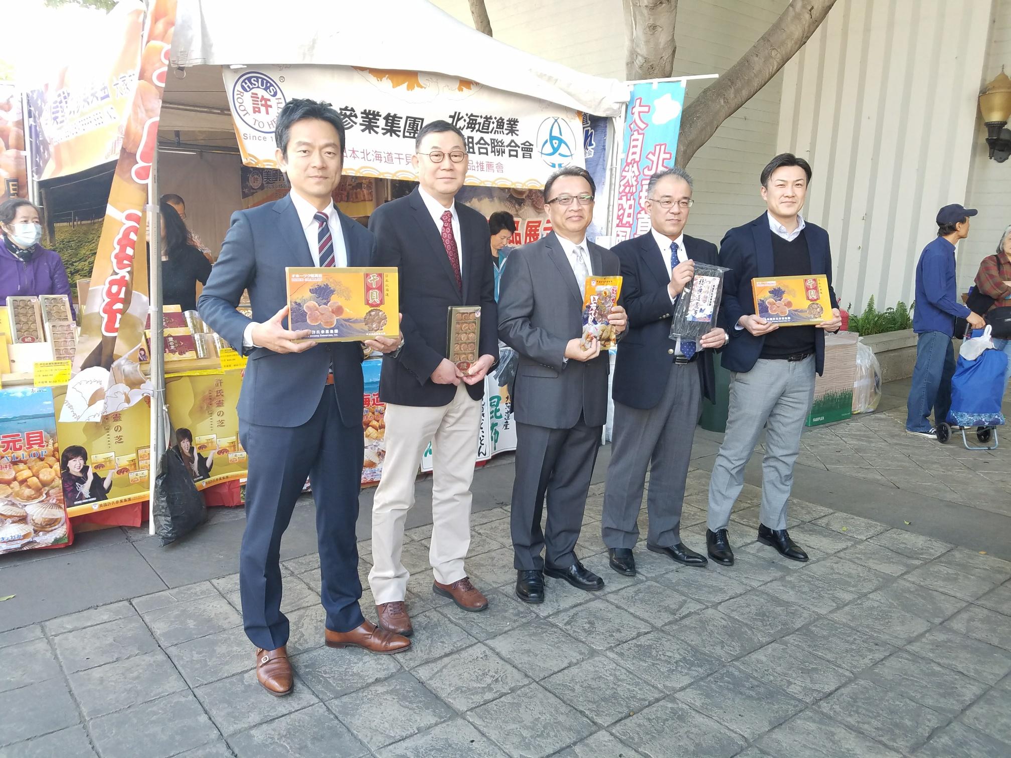 日本北海道漁業協同組合連合會總經理瀨川直樹(右2)與許氏參業集團副總裁林維章(右3)與出席嘉賓,手持許氏參業集團的產品合影。許氏參業集團提供