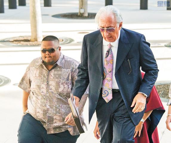 泰托(左)在律師陪同下步入法庭。美聯社