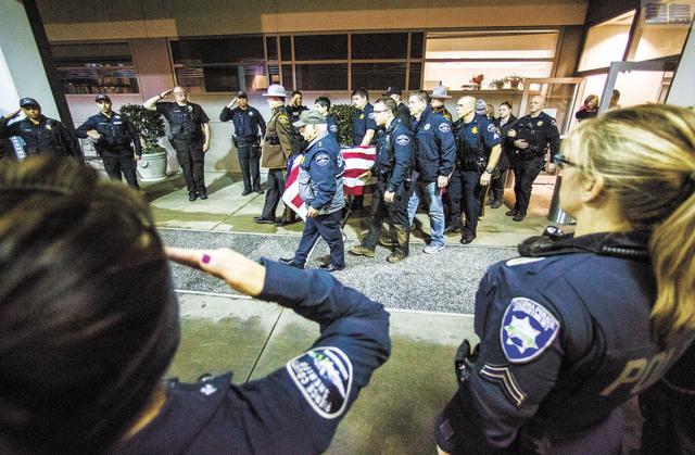 執法人員將覆蓋國旗的靈柩抬離醫院。美聯社