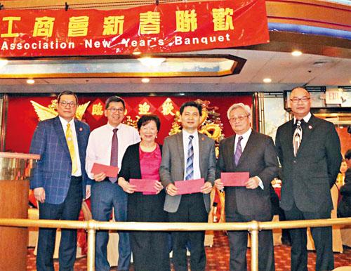 會長陳仕維(左一)、黃立輝(右一)給僑團代表發紅包。李強攝