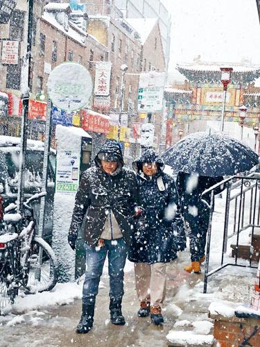 民眾在雪雨中打傘的費城華埠即景。