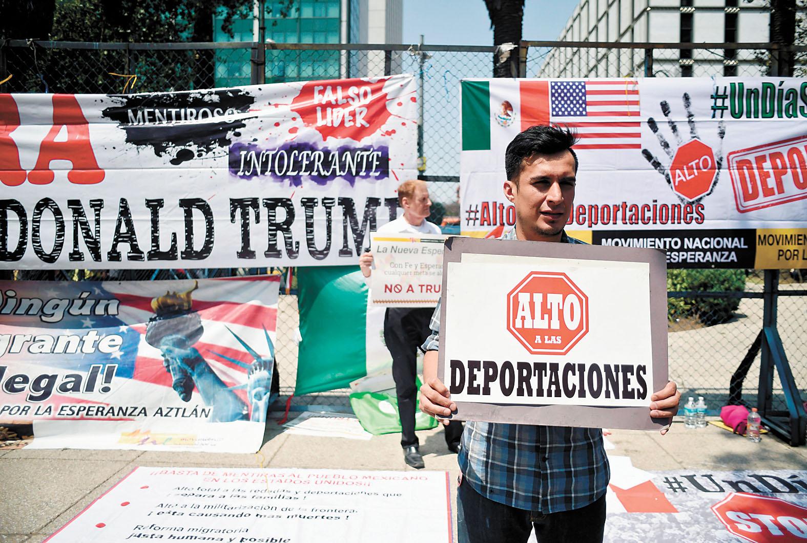 美國總統特朗普(小圖)徵收關稅的計劃引發多方批評。大圖為北美自由貿易協定第七輪談判之際,墨西哥一名男子5日在美國使館外舉牌抗議。法新社/美聯社