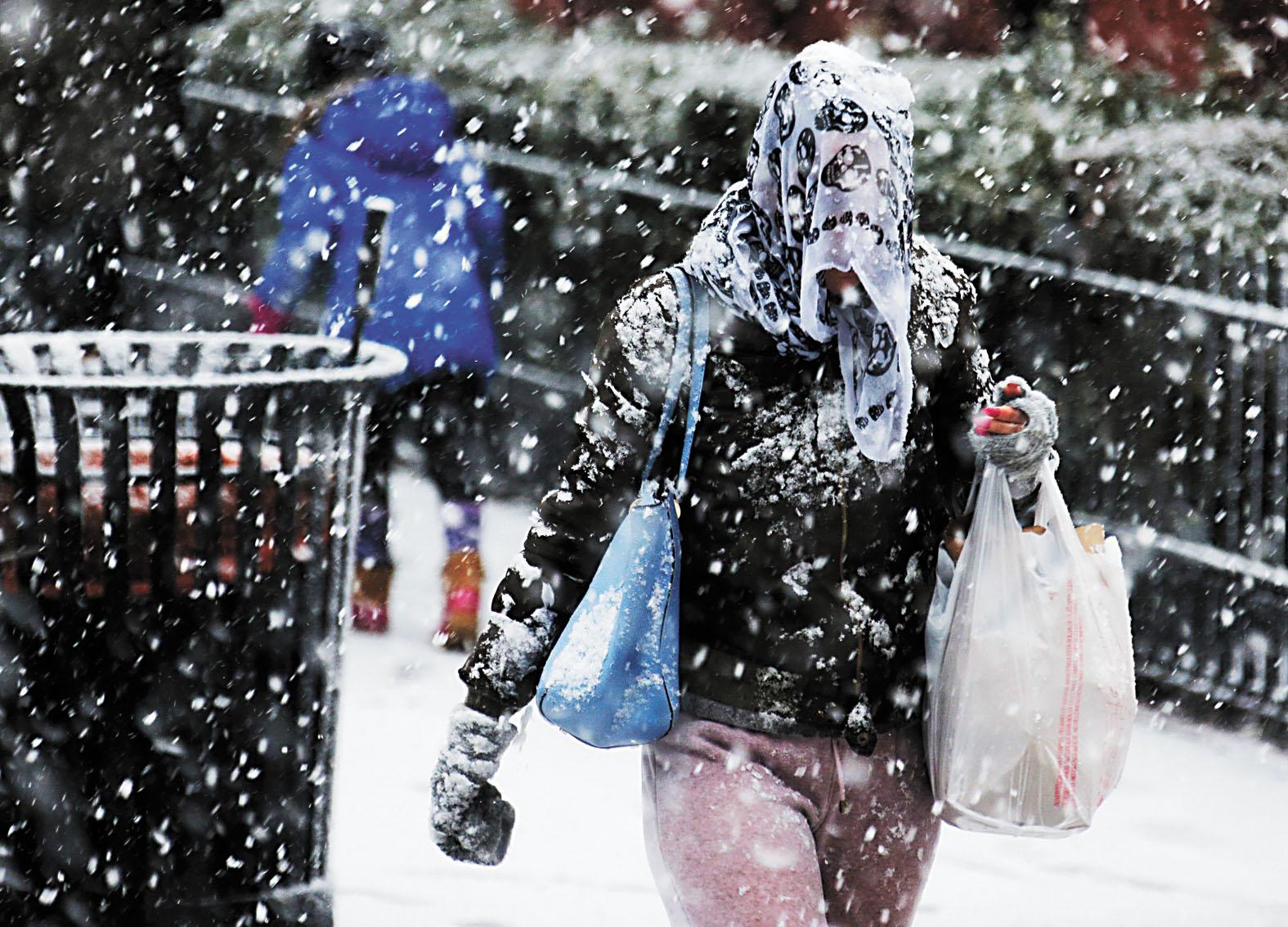 民眾在暴雪中艱難前行。美聯社
