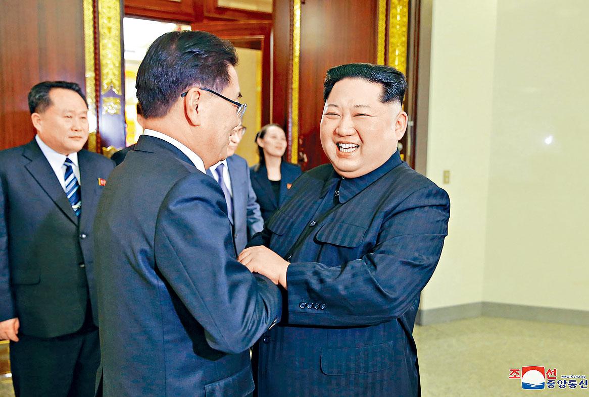金正恩與韓國特使團團長鄭義溶握手。美聯社