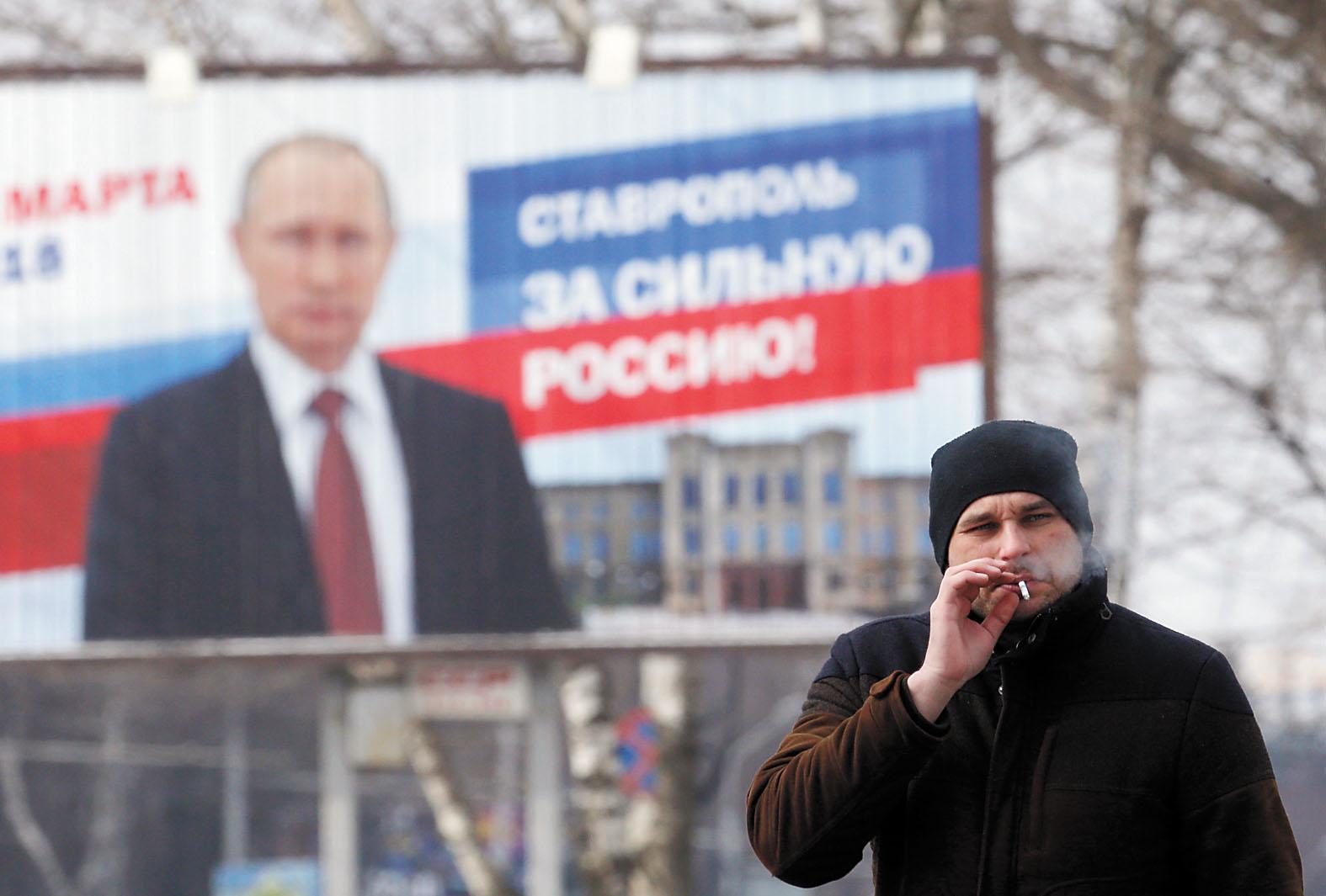 俄羅斯將於18日舉行總統大選。圖為民眾在競選展板前。路透社