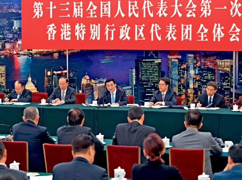 中共中央政治局常委王滬寧(中)與港澳辦主任張曉明(右二)等參加港區人大代表團的全體會議。新華社
