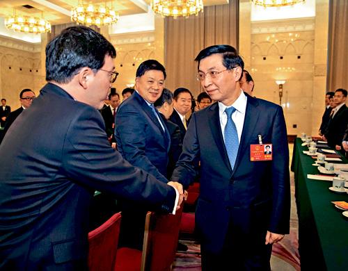 王滬寧六日在全國人大香港代表團會議上,與多名代表交流。