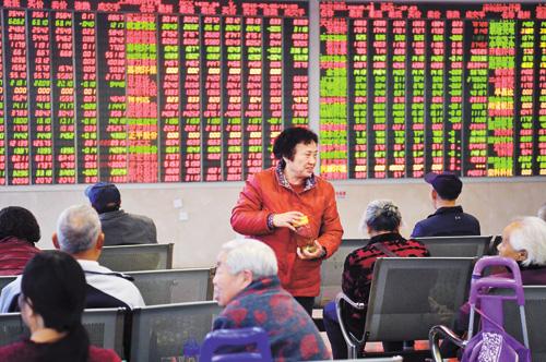 兩會期間,股市動向成為媒體關注的熱點。圖為證券營業部關注大盤走勢的股民。中新社