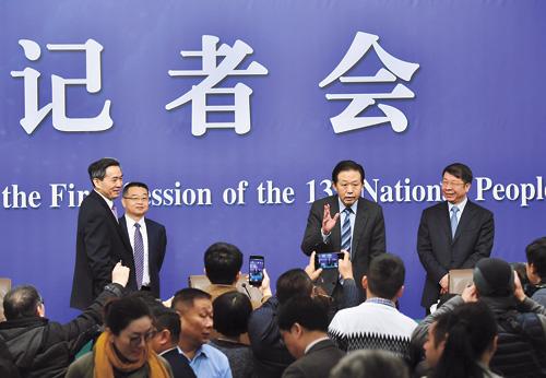 肖捷(右二)等在記者會結束後,仍被媒體記者繼續追問。新華社