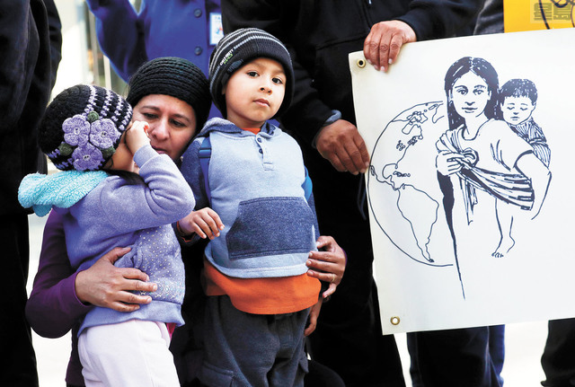 在聯邦法院外的記者會上,支持TPS計劃的Angela Henriquez(左二)安撫其子女。美聯社
