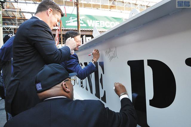 (中)市長麥法恩在建築鋼樑上簽署,慶祝工程的「封頂」階段。記者邱凱藍攝
