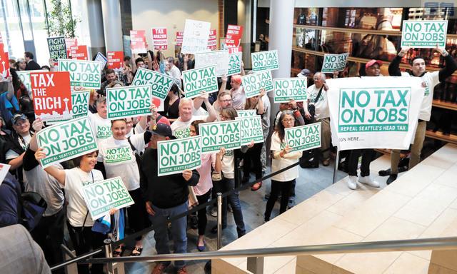 反對人頭稅的團體在市議會外舉牌抗議,成功達成目標。美聯社