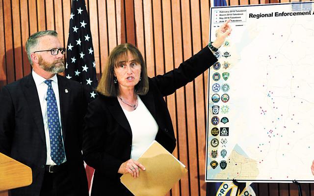 西雅圖聯邦檢控官希斯指著地圖,介紹日前執法行動。美聯社