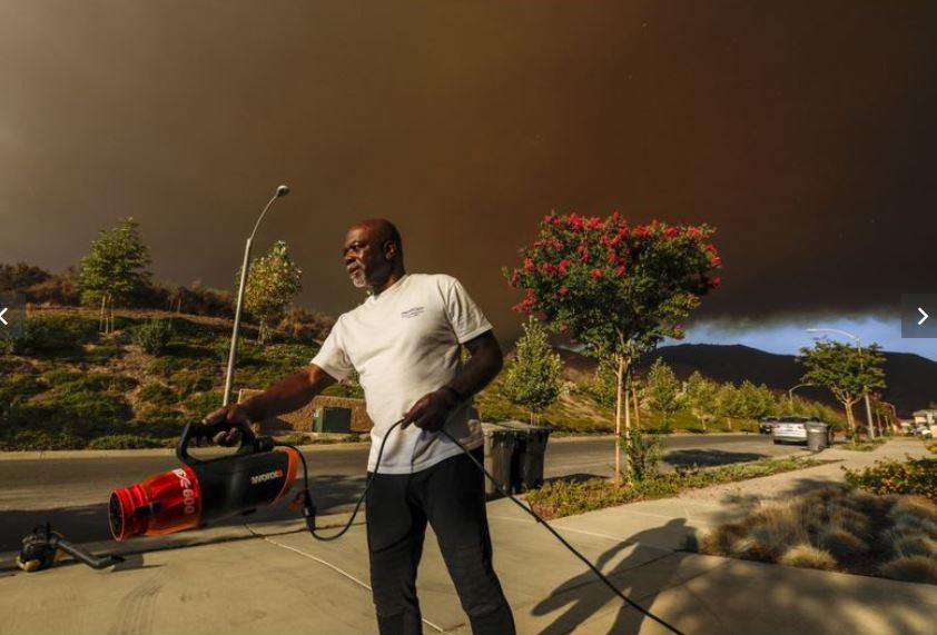 居住在科維納的民眾泰勒(Bob Tyler),他正清除山火燃燒掉落在車道上的灰燼,週遭空氣品質糟糕。洛杉磯時報