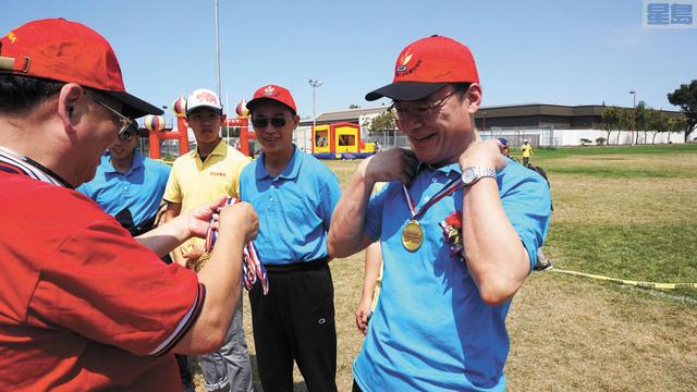 總領館獲得名人拔河賽冠軍,王東華總領事等戴上金牌。記者黃偉江攝