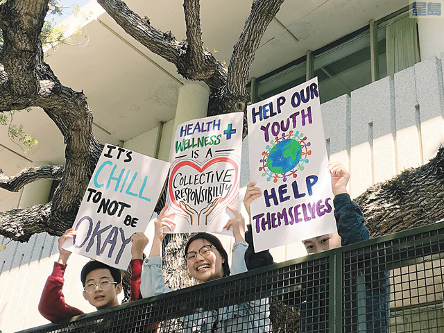 3名青少年舉起寫有「幫助青少年」和「集體責任」等訴求的標語牌。華人進步會提供