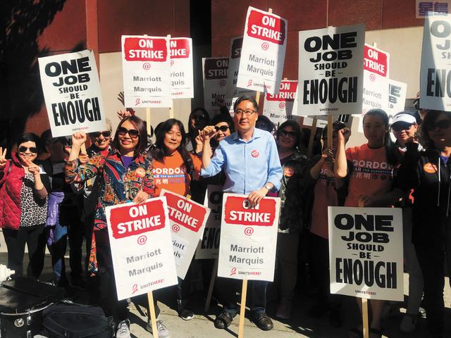 日落區市參事後選人馬兆明與數十位華裔工人參與萬豪酒店工人罷工示威。