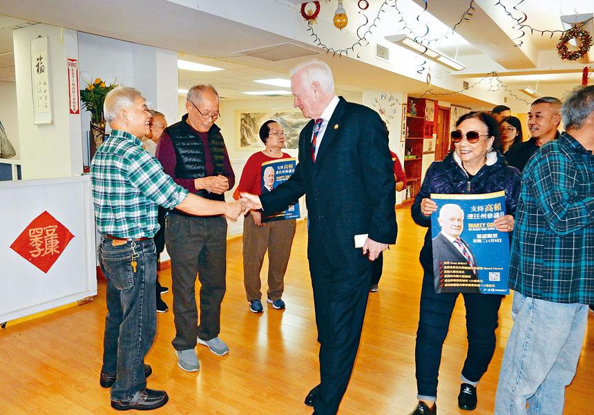 華裔選民與高頓參議員握手。 郭少華攝