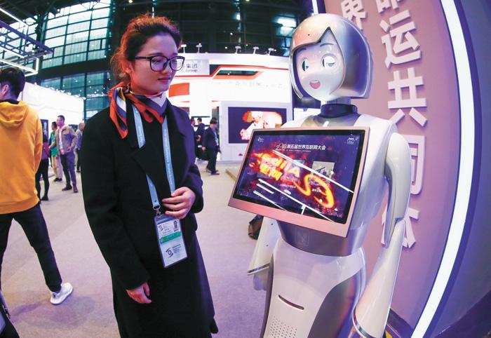 工作人員與智能機械人「小遠」互動。中新社