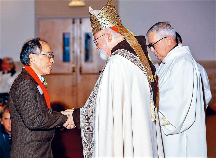 奧馬利大主教(中)給何少華(左)頒獎。陳建立提供