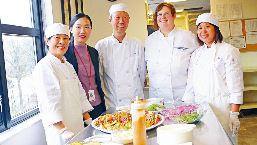 華諮處西廚訓練班12月4日對社區開放,讓民眾盡情品嚐美食與參觀廚房。烹飪導師安娜(右2),就業輔導專員趙培羽(左2)與部分學員合影。梁敏育攝