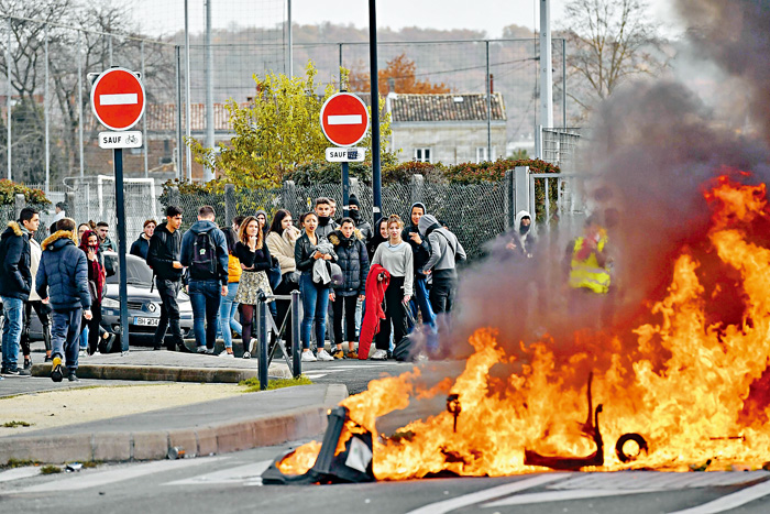 法國高中生4日在波爾多燃燒障礙物,抗議馬克龍的教育改革。法新社