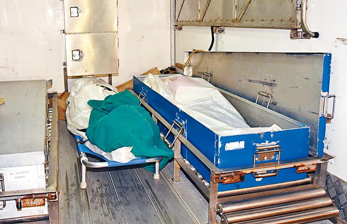 男死者(右)及其妻子遺體(左)舁送殮房。