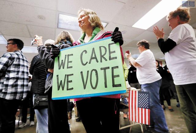 l 華州11月選舉投票率成歷史次高,圖為民眾在投票站舉牌支持民眾關心社會參與投票。美聯社