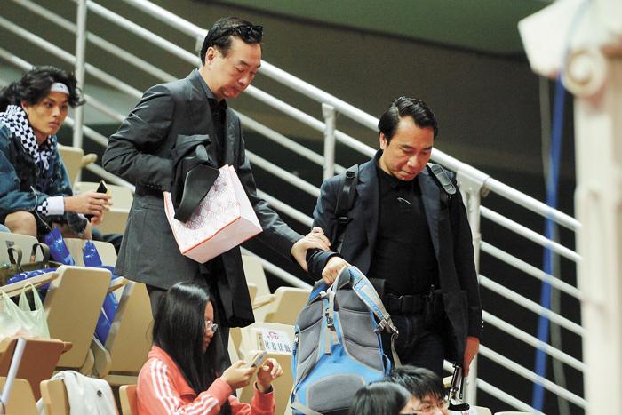 裕隆集團董事長嚴凱泰(立者左)辭世,圖為他今年3月間現身球場,觀看超級籃球聯賽(SBL) 賽事,離去時扶著保鑣的手,步下階梯。 中央社資料圖片