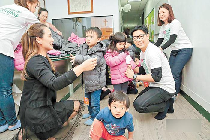 ■品冠(右2)日前與妻子(左2)一起幫育幼院的小朋友穿新衣。網上圖片