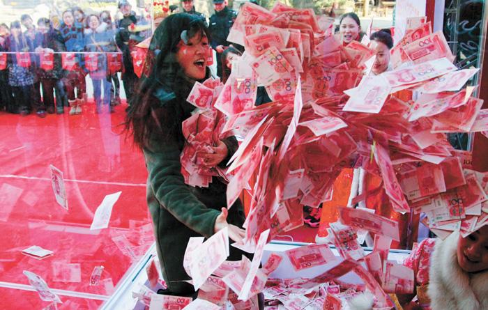 現金獎勵總是會讓人興奮。圖為杭州一家景區給遊客派發年終獎活動,在特定區域內限時一分鐘,能抓多少就帶走多少現鈔。中新社資料圖片