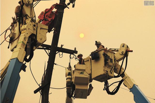 去年「營地山火」發生後,PG&E員工在天堂鎮修復電力設施。美聯社資料圖片