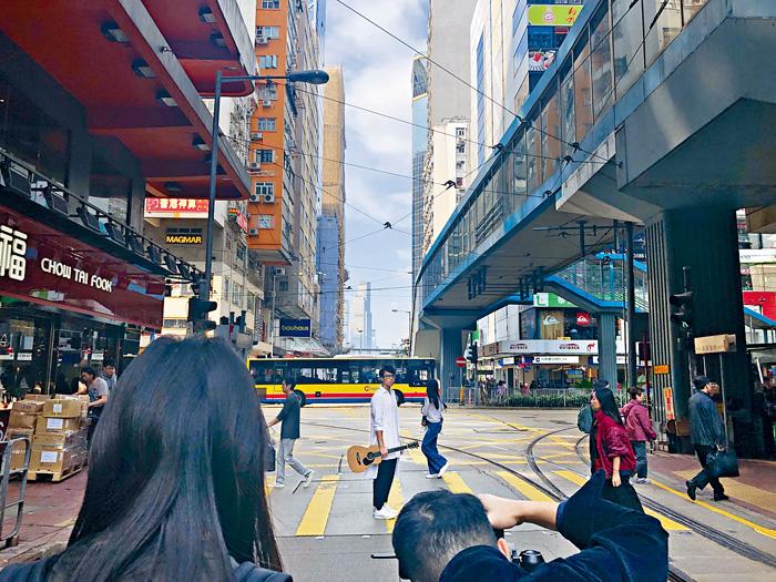 ■坤哥走到電車路上,拍攝演唱會海報。