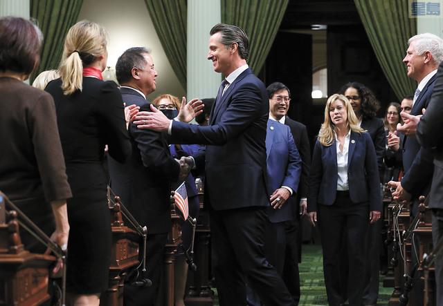 紐森進場發表州情咨文,與華裔議員丁右立握手。美聯社
