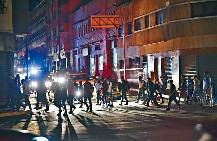 委內瑞拉首都加拉加斯在7日晚停電,市民摸黑外出。 法新社
