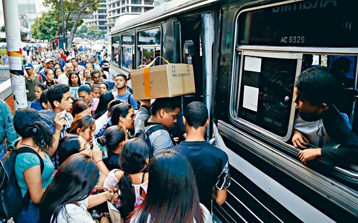 大停電後,加拉加斯市民湧往擠巴士。 美聯社