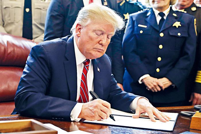 ■特朗普總統行使否決權,在白宮橢圓形辦公室簽署文件推翻國會阻止緊急狀態令的決議案。    美聯社