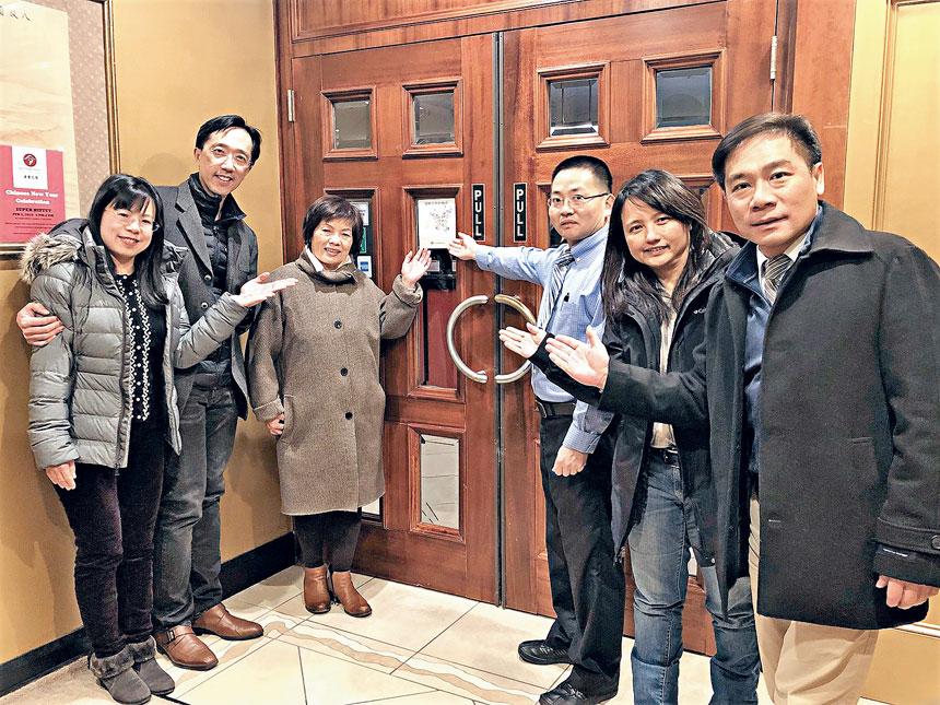 徐小玲(左三)在餐館大門張貼認證貼紙,與徐佑典夫婦(左一、左二)、歐宏偉(右一)合影。