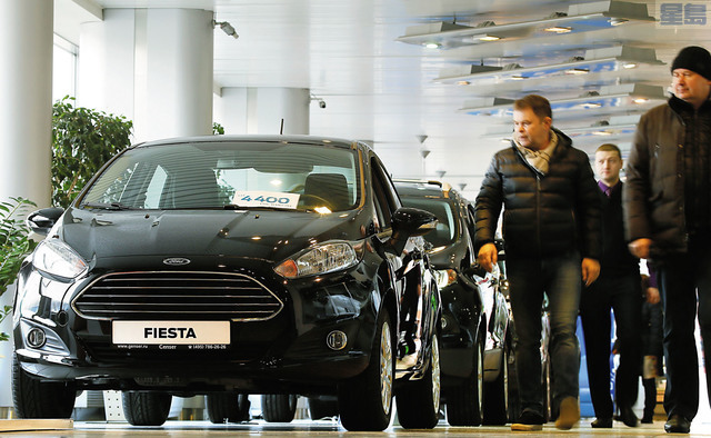 福特汽車公司將繼續擴大自動駕駛汽車測試力,圖為經銷商走過福特汽車。路透社資料圖片