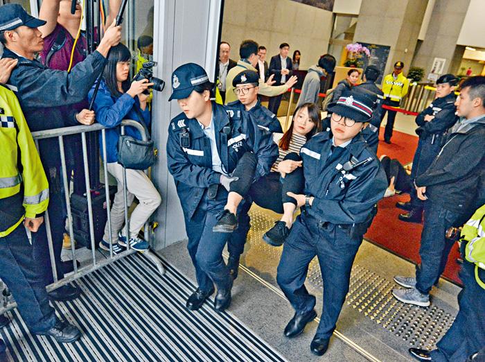 警員把闖入政總的香港眾志成員逐一抬走。 蔡建新攝