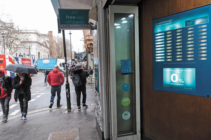 在英國倫敦,人們14日從一處貨幣兌換點旁走過。新華社