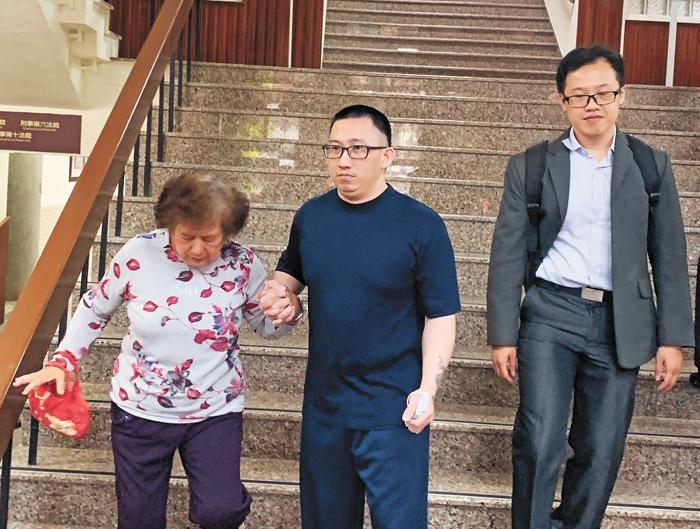台南高分院14日裁定再審遭控犯下台南歸仁雙屍命案的謝志宏(中),並停止刑罰執行,遭羈押迄今已19年的謝志宏下午獲釋,緊牽母親的手,難掩開心。中央社