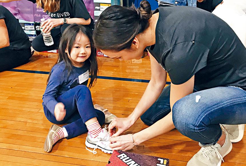 小學生在志願者的幫助下試穿新鞋。