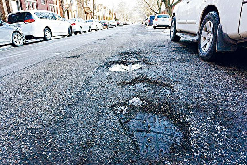 一個嚴寒的冬天過去了,芝加哥街道的坑洞日益嚴重,極易造成車子的損壞。梁敏育攝