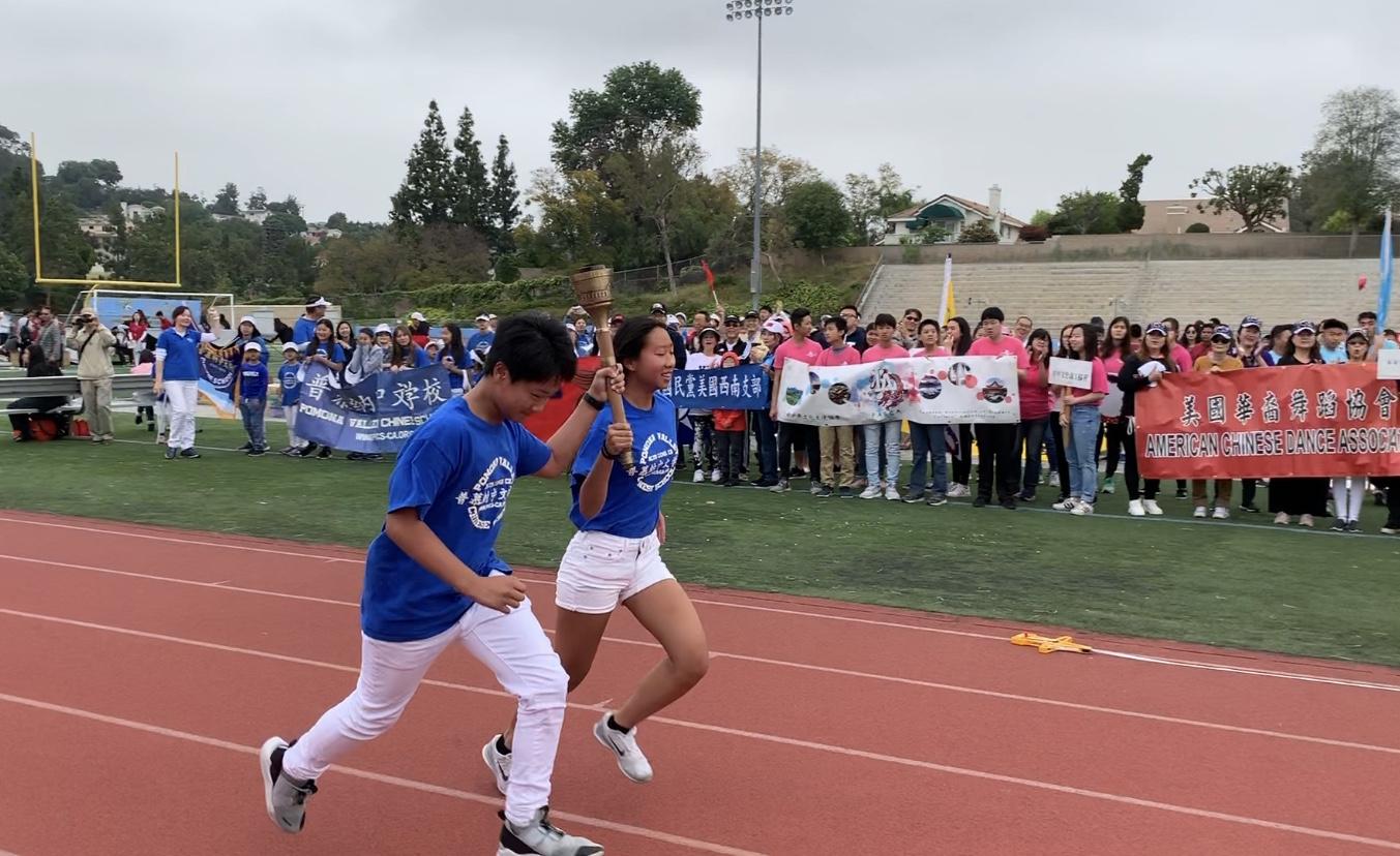 兩位去年表現優秀的青年代表選手,手持1984年洛杉磯奧運聖火火炬繞場,為海華運動會揭開序幕。記者黃品瑄攝