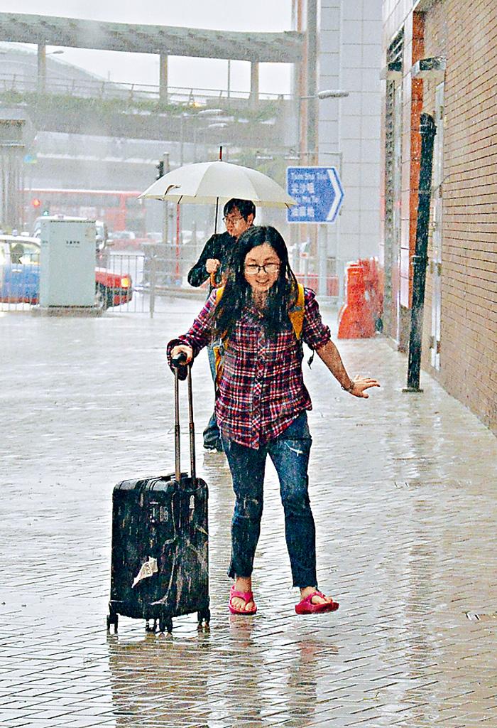 ■忽然大雨,沒帶雨遮的拖篋女孩狂奔避雨,十分狼狽。郭顯熙攝