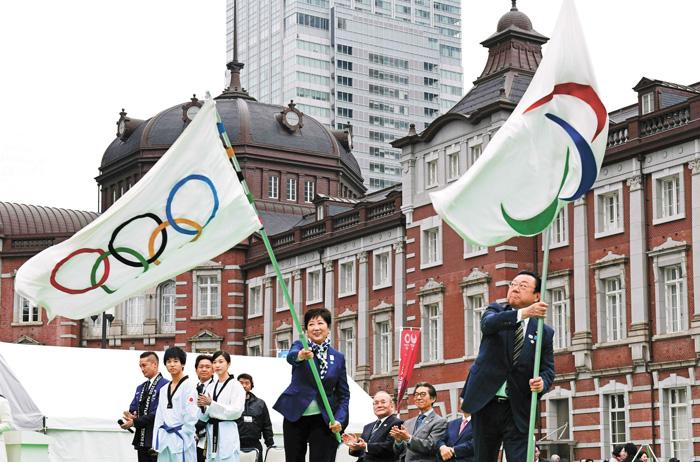 東京奧運會將在明年舉辦,圖為東京都知事和東京奧運會部長在揮舞展示2020年東京奧運會和殘奧會會旗。法新社資料圖片